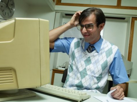 Man working at office desk, looking at computer and scratching head