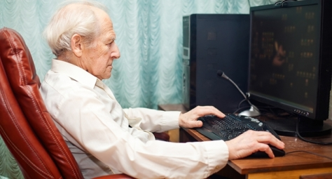 old man sitting in a chair and working with computer