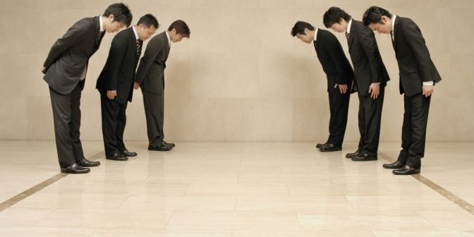 Two groups of businessmen bowing to each other, side view